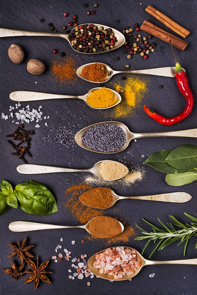 mix of colorful spices and aromatic herbs on a slate stone